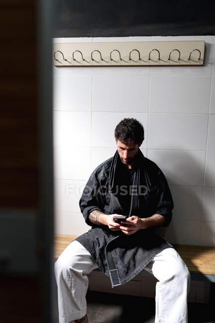 Sério adulto descalço macho em quimono sentado no banco em camarim e navegando smartphone enquanto descansa após o treinamento na escola de artes marciais — Fotografia de Stock