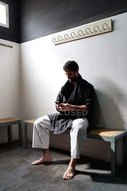 Positivo adulto descalço macho em quimono sentado no banco em camarim e navegando smartphone enquanto descansa após o treinamento na escola de artes marciais — Fotografia de Stock