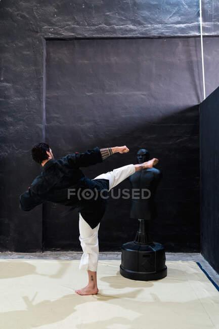 Vista posterior de luchador masculino irreconocible realizando ejercicio de patada alta con maniquí de boxeo durante el entrenamiento kajukenbo en el club de artes marciales - foto de stock