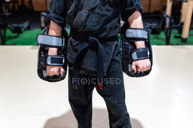 Cropped unrecognizable powerful adult martial arts master in black kimono and boxing pads standing in modern club with sports equipment — Stock Photo