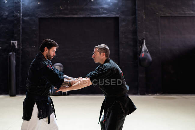Side view of male martial art masters fighting while practicing self defense technique during kajukenbo training in modern club — Stock Photo