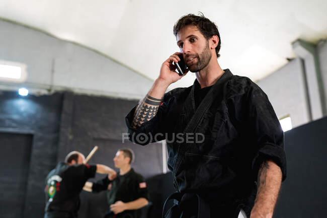Vue latérale d'un homme adulte sérieux en kimono noir debout près d'un banc avec un grand sac de sport et parlant sur un téléphone portable tout en se reposant pendant l'entraînement dans une école d'arts martiaux — Photo de stock