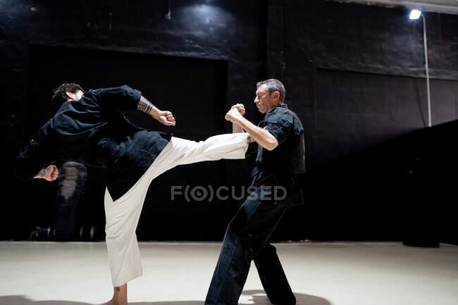 Vista lateral de lutador masculino adulto em quimono realizando ataque pontapé contra parceiro durante o treinamento de kajukenbo na moderna escola de artes marciais — Fotografia de Stock