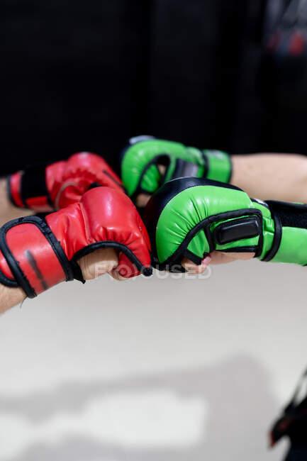 Seitenansicht der Ernte anonyme männliche Kampfsportler in roten und grünen Boxhandschuhen, die sich vor dem Kampf begrüßen — Stockfoto