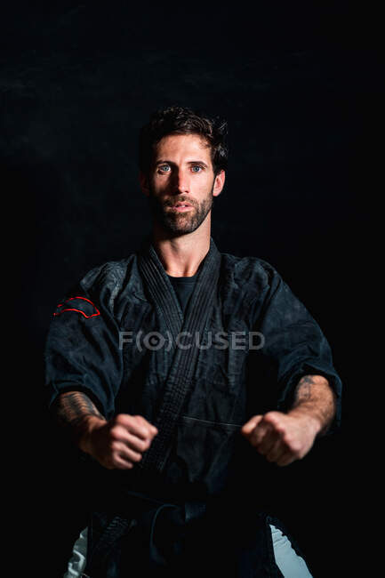 Confident adult bearded martial arts practitioner with tattooed arms standing in defensive fighting pose against black background — Stock Photo