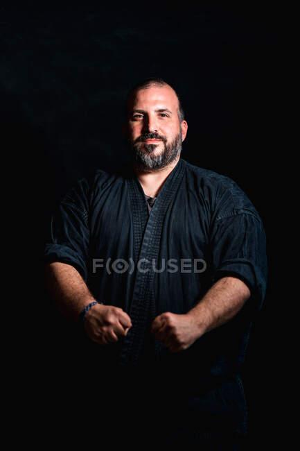 Selbstbewusster erwachsener bärtiger Kampfsportler mit tätowierten Armen, der in defensiver Kampfpose vor schwarzem Hintergrund steht — Stockfoto