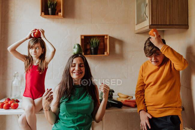 Mulher adulta e irmãos segurando pimentas coloridas e orando na cozinha acolhedora em casa — Fotografia de Stock