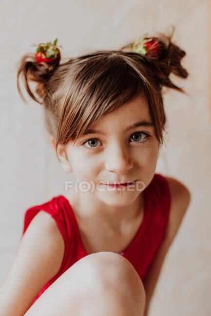 Adorable chica con fresas frescas en bollos de pelo sonriendo y mirando a la cámara - foto de stock