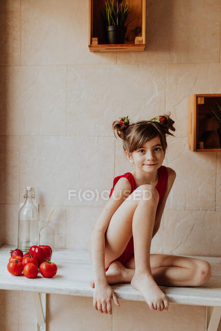 Cute barefoot girl in red bodysuit sitting on counter with tomatoes and red pepper in kitchen — Stock Photo