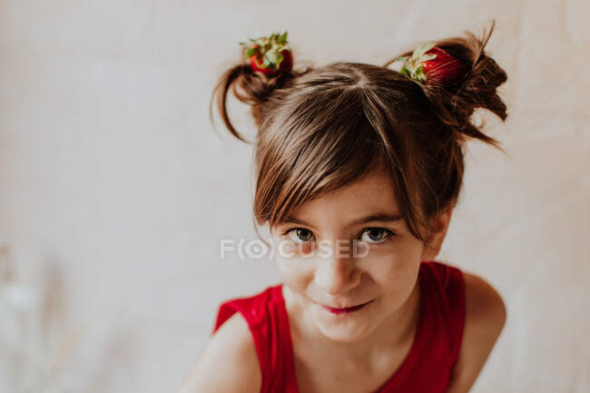 Adorable girl with fresh strawberries in hair buns smiling and looking at camera — Stock Photo