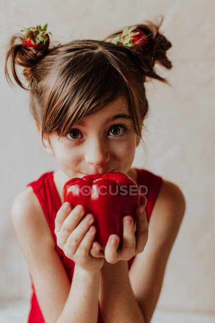 Adorable little girl with strawberries in hair showing fresh pepper and looking at camera — Stock Photo
