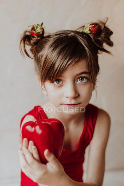 Adorable niña con fresas en el pelo mostrando pimienta fresca y mirando a la cámara - foto de stock