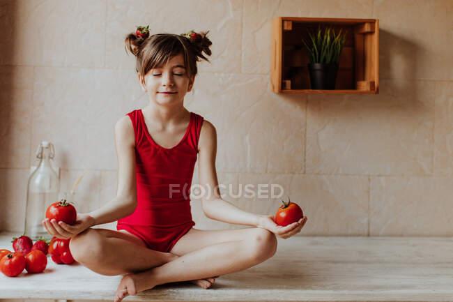 Милая босиком девушка в красном купальнике сидит скрестив ноги на прилавке и медитирует с помидорами на кухне — стоковое фото