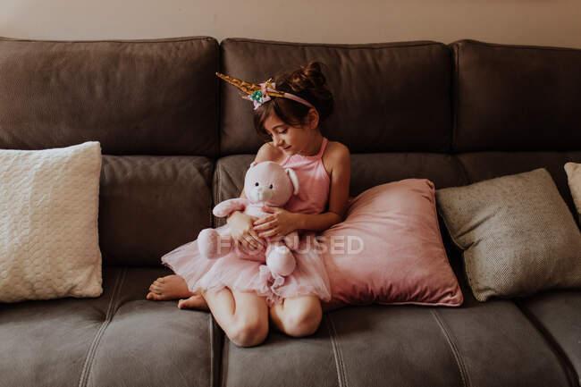 Босоногая девушка в костюме единорога обнимает плюшевую игрушку, отдыхая дома на удобном диване — стоковое фото