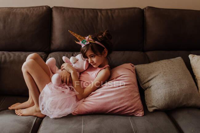 Vista laterale della ragazza scalza in costume da unicorno che abbraccia peluche mentre riposa su un comodo divano a casa — Foto stock