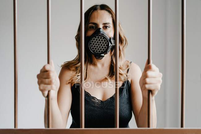 Young female in protective respirator mask and black dress standing behind metal fence and looking at camera while representing concept of coronavirus prevention and isolation — Stock Photo