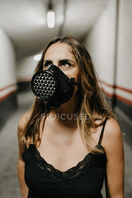 Jovem mulher alegre em vestido preto elegante e máscara respirador preto olhando para cima, enquanto está em pé no corredor estreito dentro do edifício — Fotografia de Stock