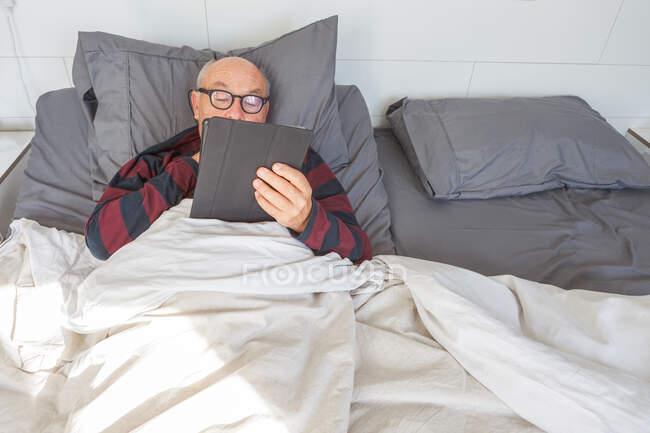 Старший чоловік у окулярах лежить у ліжку, використовуючи планшет під час ранкового перебування вдома. — стокове фото
