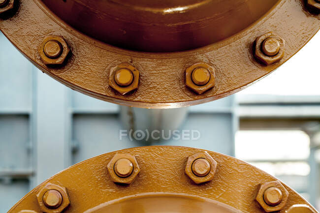 Closeup of steel joint connecting flanges with bolts and nuts on pipe transferring liquids at factory — Stock Photo