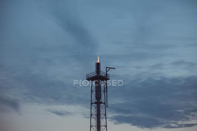 Будівництво нафтопереробного заводу з вогнем у хмарному небі в сутінках. — стокове фото