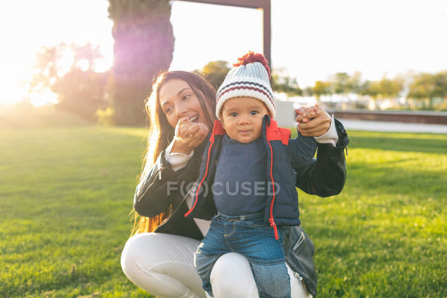 Cheerful young woman holding cute toddler kid in warm wear while spending sunny autumn day on green meadow in park — Stock Photo