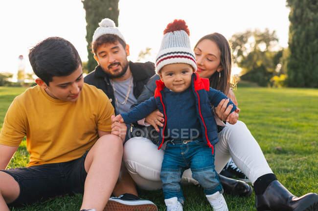 Allegro giovane uomo e donna con ragazzo adolescente e bambino bambino sorridente e guardando la fotocamera mentre seduti su plaid sull'erba verde e godendo del tempo insieme nella soleggiata giornata autunnale nel parco — Foto stock