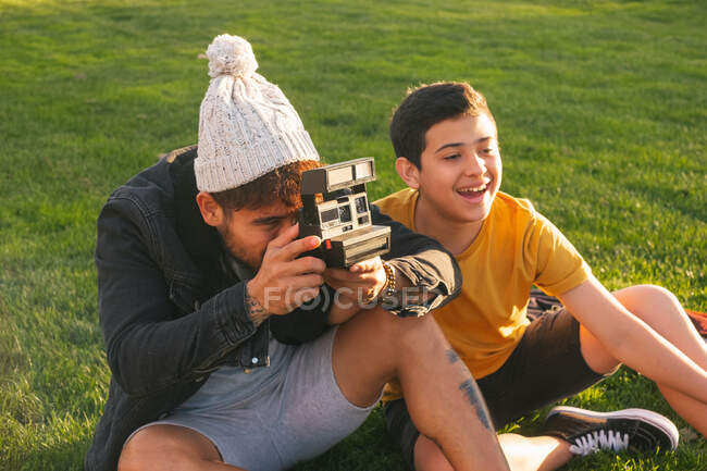 Jeune homme avec appareil photo instantané assis sur l'herbe près de fils adolescent et de prendre une photo de femme gaie avec petit enfant tout en passant du temps ensemble dans le parc d'automne — Photo de stock
