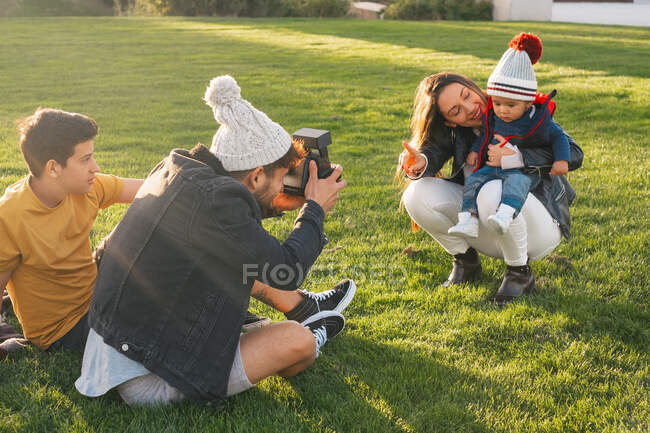 Young man with instant camera sitting on grass near teen son and taking photo of cheerful wife with little child while spending time together in autumn park — Stock Photo
