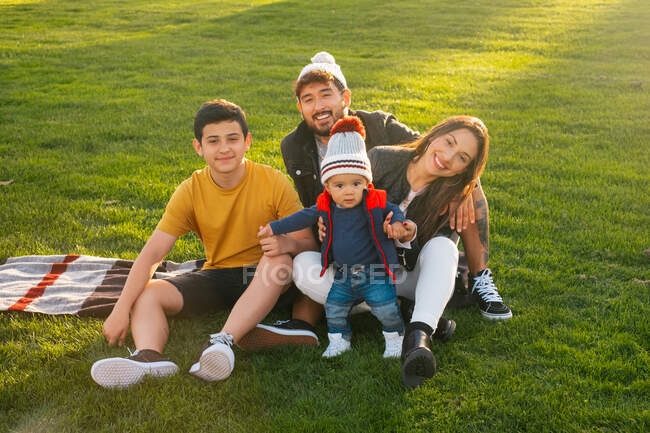 Cheerful young man and woman with teen boy and toddler kid smiling and looking at camera while sitting on plaid on green grass and enjoying time together in sunny autumn day in park — Stock Photo