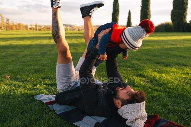 Vue latérale du jeune homme joyeux couché sur la couverture sur l'herbe verte et tenant mignon tout-petit enfant en tenue chaude tout en se reposant pendant le week-end dans le parc — Photo de stock