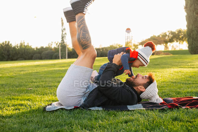 Side view of cheerful young man lying on blanket on green grass and holding cute toddler kid in warm wear while resting during weekend in park — Stock Photo