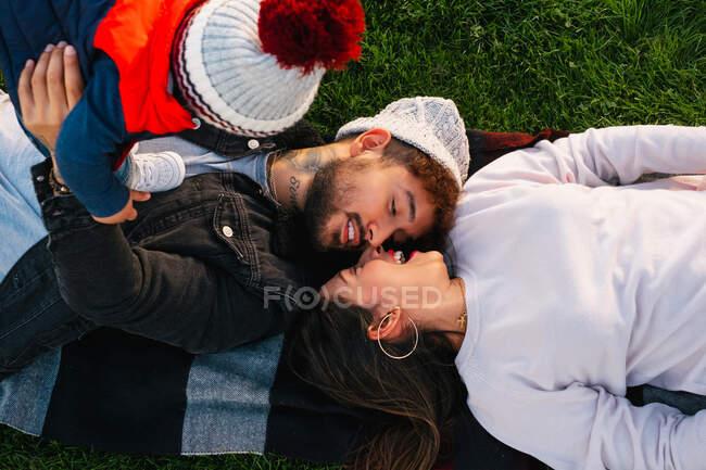 Над веселим молодим подружжям з маленькою дитиною лежить на штукатурці на зеленій траві і проводить разом час у парку. — стокове фото
