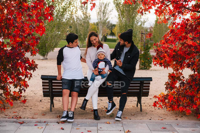 Positive man and woman with teen boy and little toddler leaning on wooden bench framed by branches of red autumn trees in park — Stock Photo