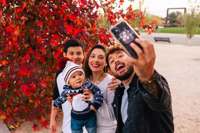 Jovens pais felizes com crianças tirando selfie com smartphone enquanto estão perto da árvore vermelha no dia de outono no parque — Fotografia de Stock