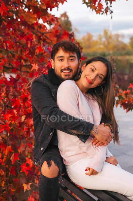 Счастливый молодой человек и женщина обнимаются, сидя на скамейке возле красочного осеннего дерева в парке — стоковое фото