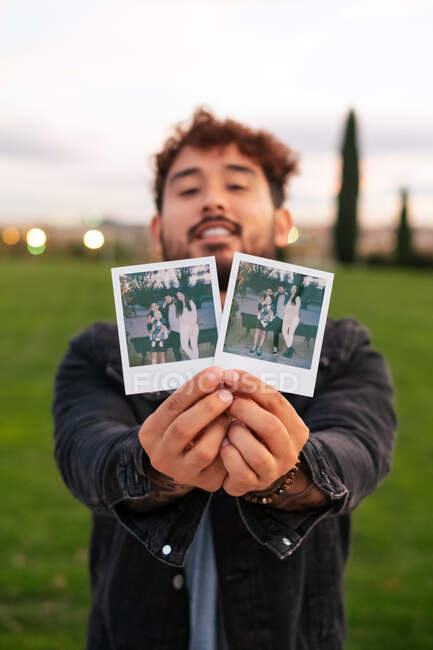 Cheerful young man in casual wear standing on green lawn and demonstrating instant photos of family — Stock Photo