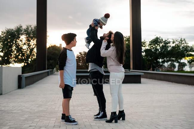Vue latérale du père heureux jetant petit enfant tout en se tenant avec sa femme et son fils aîné sur la place de la ville dans la soirée ensoleillée — Photo de stock