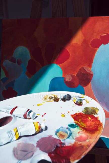 Грязная палитра с пятнами пигмента и трубки помещены возле мольберта с абстрактной росписью — стоковое фото