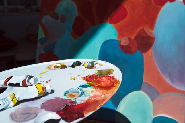 Messy palette with stains of pigment and tubes placed near easel with abstract painting — Stock Photo