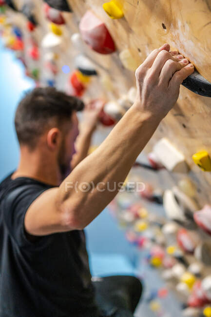 From above side view of crop male athlete in sportswear with hands in talcum powder holding on grips training in gym — Stock Photo