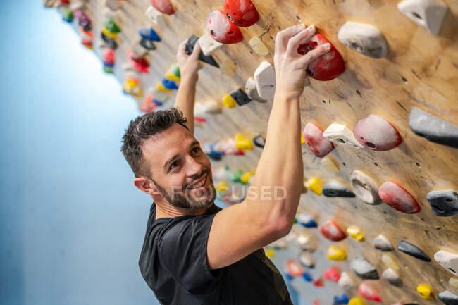 Vue latérale d'un athlète masculin heureux et fort regardant une caméra en tenue de sport grimper sur un mur coloré pendant l'entraînement dans un gymnase moderne — Photo de stock