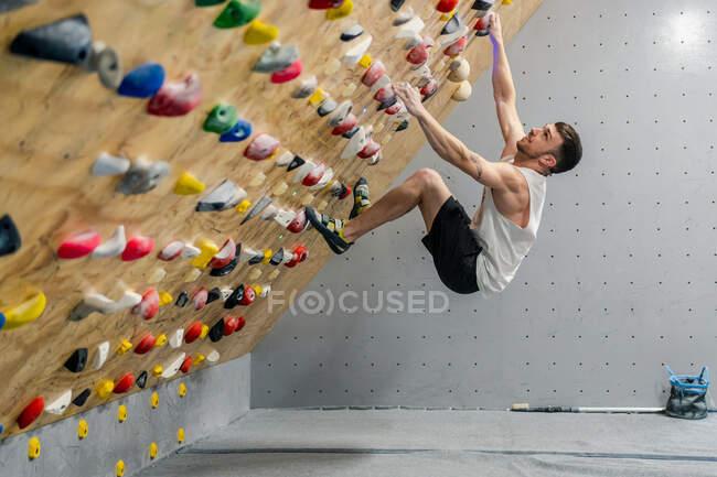 De vue de côté de soufflet de l'athlète masculin fort dans l'escalade de vêtements de sport sur le mur coloré pendant l'entraînement chez le gars moderne — Photo de stock
