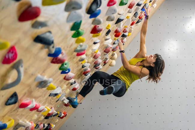 Vue latérale d'en bas de la femme concentrée en vêtements de sport suspendus sur un mur escarpé au-dessus des tapis dans le centre d'escalade moderne — Photo de stock