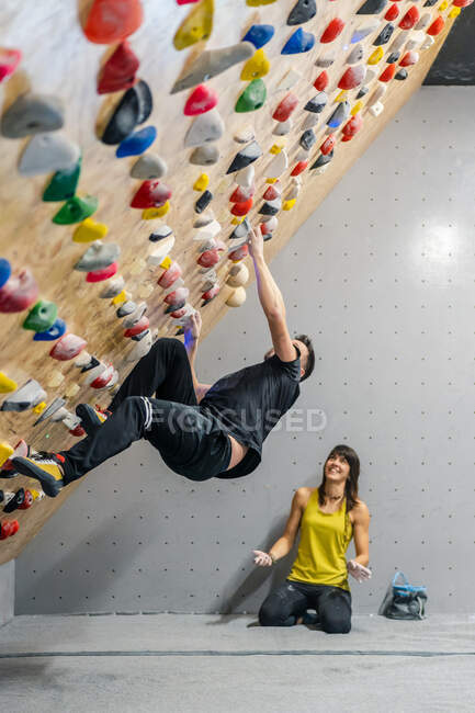 Side view of male athlete in active wear climbing on grips during bouldering workout with satisfied female sitting near in gym — Stock Photo