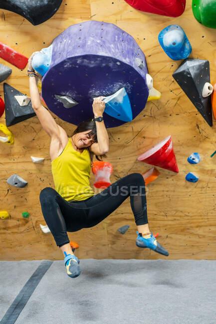 Jeune grimpeuse aux cheveux noirs en tenue active souriante accrochée à une grande poignée de mur d'escalade dans un gymnase — Photo de stock