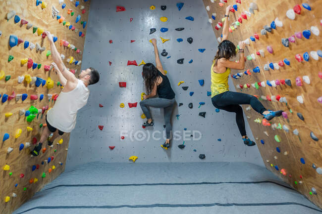 Side view of young group of strong male and female climbers having training on wall in modern gym — Stock Photo