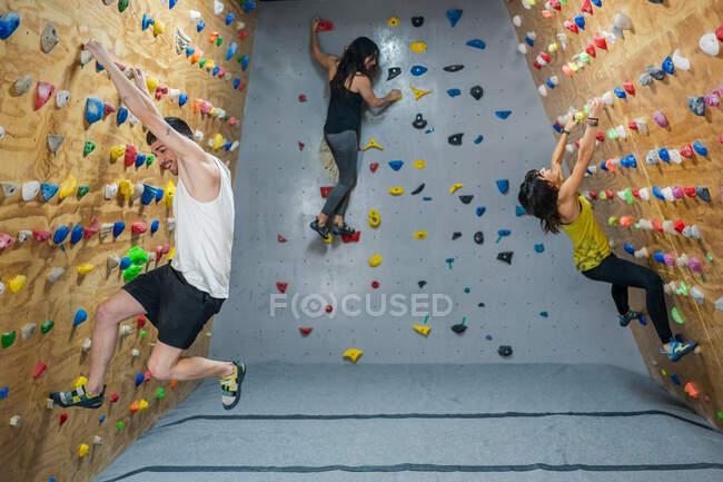 Vue latérale d'un jeune groupe d'alpinistes forts, hommes et femmes, s'entraînant au mur dans une salle de gym moderne — Photo de stock
