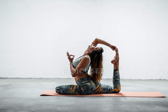 Вид сбоку сидящей на коврике и практикующей йогу Эка Пада Раджакапотасана с жестом мудра — стоковое фото
