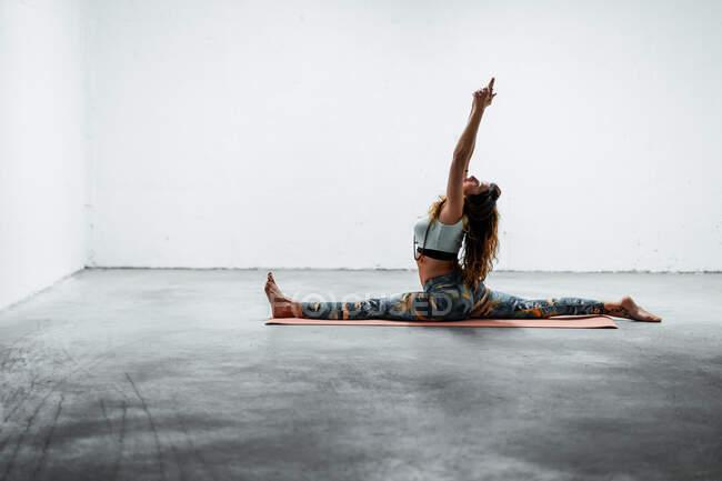 Вид сбоку на молодую гибкую женщину в костюме, делающую передний разрез с поднятыми руками, сидя на полу — стоковое фото