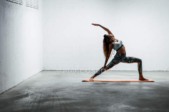 Вид сбоку на спокойную женщину в спортивных леггинсах и лифчике, стоящую на коврике в позе воина наоборот, глядя вверх — стоковое фото